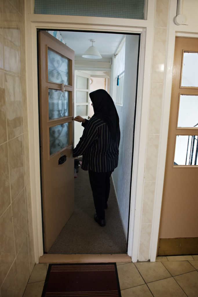 A photo of a lady in a headscarf opening the front door to her flat, provided by the Destitute Asylum Seeker Service (DASS)